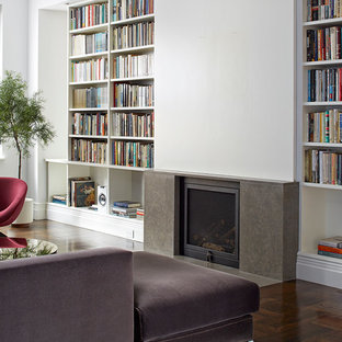 Photo of a mid-sized contemporary open concept living room in New York with white walls, medium hardwood floors, a standard fireplace, a concrete fireplace surround and a concealed tv.