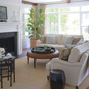 Idee per un grande soggiorno classico chiuso con sala formale, pareti bianche, pavimento in legno massello medio, camino classico, cornice del camino in legno e TV nascosta