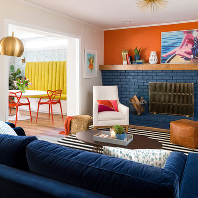 Living room - eclectic enclosed light wood floor living room idea in Atlanta with a standard fireplace, a brick fireplace, orange walls and no tv