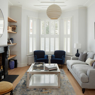 Design ideas for a traditional formal enclosed living room in London with white walls, light hardwood flooring, a standard fireplace and beige floors.