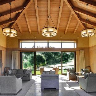 Esempio di un soggiorno country aperto con sala formale, pareti beige, camino classico, cornice del camino in pietra, parete attrezzata e pavimento in ardesia