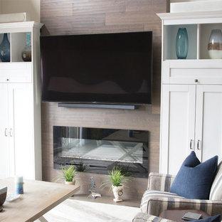 トロントの大きいビーチスタイルのおしゃれな独立型リビング (フォーマル、ベージュの壁、淡色無垢フローリング、吊り下げ式暖炉、木材の暖炉まわり、埋込式メディアウォール、グレーの床) の写真