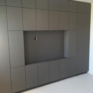 Diseño de salón minimalista con paredes blancas, moqueta y pared multimedia