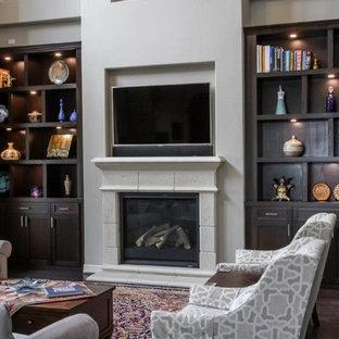 Immagine di un grande soggiorno con camino classico, cornice del camino in cemento e TV a parete