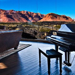 フェニックスの広いサンタフェスタイルのおしゃれなLDK (ベージュの壁、濃色無垢フローリング、標準型暖炉、石材の暖炉まわり、ミュージックルーム、茶色い床) の写真