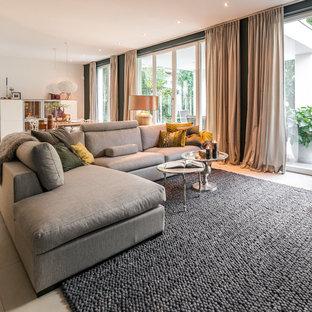 Idées déco pour un salon ouvert avec un mur vert, béton au sol, un sol beige et du papier peint.