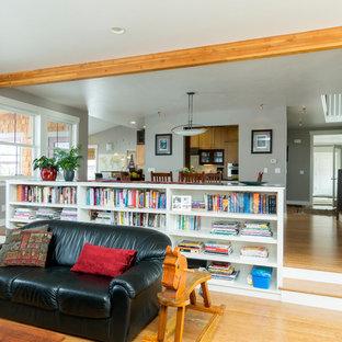 Immagine di un soggiorno bohémian di medie dimensioni e aperto con pareti grigie, pavimento in bambù, libreria, nessuna TV, camino classico e cornice del camino in pietra