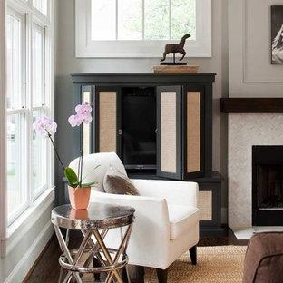 Imagen de salón abierto, actual, de tamaño medio, con paredes grises, suelo de madera oscura, chimenea tradicional y televisor retractable