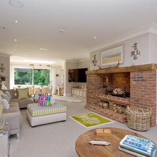 ロンドンのトラディショナルスタイルのおしゃれなLDK (グレーの壁、カーペット敷き、標準型暖炉、レンガの暖炉まわり、壁掛け型テレビ) の写真