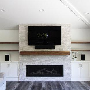 Exempel på ett stort klassiskt allrum med öppen planlösning, med vita väggar, vinylgolv, en bred öppen spis, en inbyggd mediavägg och brunt golv