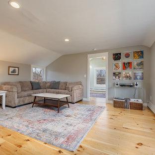 Foto de salón cerrado, de estilo de casa de campo, de tamaño medio, con paredes grises, suelo de madera clara, chimenea de esquina, marco de chimenea de ladrillo, televisor independiente y suelo beige