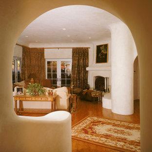 Idée de décoration pour un très grand salon avec une bibliothèque ou un coin lecture sud-ouest américain ouvert avec un mur beige, un sol en carrelage de céramique, une cheminée standard, un manteau de cheminée en brique et un téléviseur encastré.