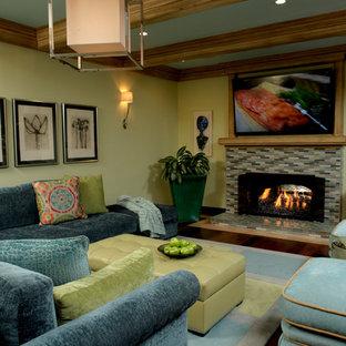 オレンジカウンティの広いトラディショナルスタイルのおしゃれなリビング (緑の壁、標準型暖炉、タイルの暖炉まわり、濃色無垢フローリング、壁掛け型テレビ) の写真