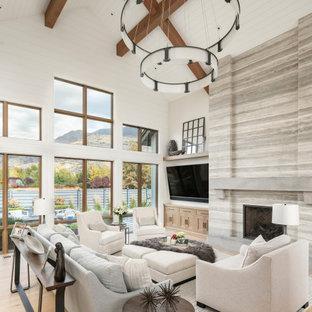 Inspiration för mycket stora lantliga allrum med öppen planlösning, med vita väggar, ljust trägolv, en standard öppen spis, en spiselkrans i sten, en väggmonterad TV och beiget golv