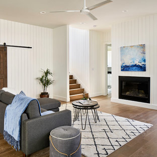Coastal medium tone wood floor living room photo in Austin with white walls, a ribbon fireplace and no tv