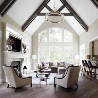 Idée de décoration pour un salon tradition ouvert avec une salle de réception, un mur gris, un sol en bois foncé, une cheminée standard et un téléviseur fixé au mur.