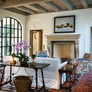 マイアミの中サイズの地中海スタイルのおしゃれなLDK (フォーマル、白い壁、コンクリートの床、標準型暖炉、木材の暖炉まわり、テレビなし、グレーの床) の写真