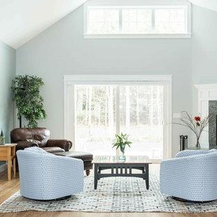 ポートランド(メイン)の大きいトラディショナルスタイルのおしゃれなリビング (グレーの壁、クッションフロア、コーナー設置型暖炉、石材の暖炉まわり、茶色い床) の写真