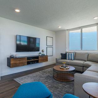 タンパのビーチスタイルのおしゃれなリビング (白い壁、濃色無垢フローリング、壁掛け型テレビ) の写真