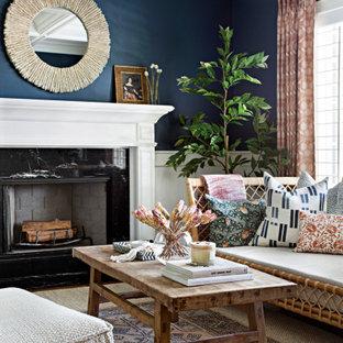 Bild på ett vintage vardagsrum, med blå väggar, en standard öppen spis och en spiselkrans i sten