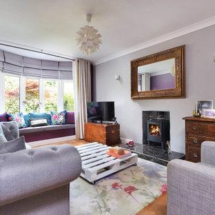 Imagen de salón cerrado, tradicional renovado, de tamaño medio, con paredes púrpuras, televisor independiente y estufa de leña