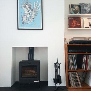 Foto de salón con rincón musical actual, pequeño, con suelo de bambú, estufa de leña y paredes blancas
