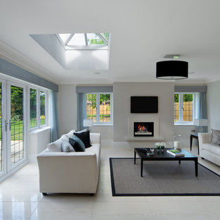 Inspiration for a contemporary living room in Sussex with white walls, a standard fireplace, a wall mounted tv and white floors.