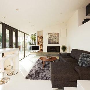 Mittelgroßes Modernes Wohnzimmer mit weißer Wandfarbe, Kamin, freistehendem TV, Betonboden und weißem Boden in Vancouver