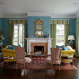 Design ideas for a classic enclosed living room in London with blue walls, dark hardwood flooring, a standard fireplace, a stone fireplace surround and brown floors.