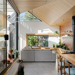 Foto de salón abierto, contemporáneo, de tamaño medio, con paredes blancas, suelo de cemento, estufa de leña, televisor independiente y suelo gris