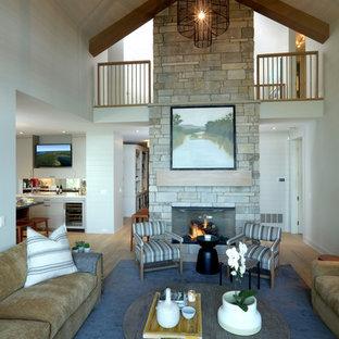 Immagine di un soggiorno chic aperto e di medie dimensioni con pareti bianche, parquet chiaro, camino bifacciale, cornice del camino in pietra, TV a parete e pavimento marrone