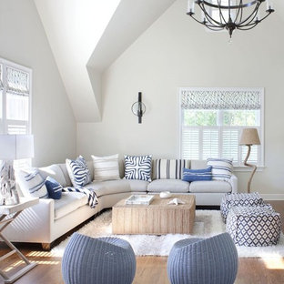 Coastal medium tone wood floor and brown floor living room photo in New York with white walls