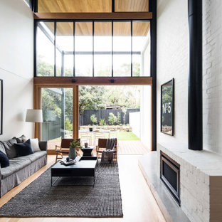Design ideas for a mid-sized contemporary loft-style living room in Sydney with white walls, medium hardwood floors, a standard fireplace, a brick fireplace surround and timber.