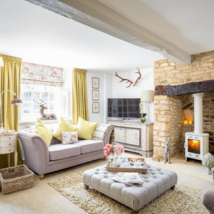 This is an example of a large rustic formal enclosed living room in Gloucestershire with white walls, carpet, a wood burning stove, a stone fireplace surround and a freestanding tv.