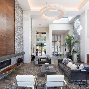 ポートランドの巨大なコンテンポラリースタイルのおしゃれなLDK (磁器タイルの床、コーナー設置型暖炉、石材の暖炉まわり、グレーの床、フォーマル、マルチカラーの壁、テレビなし) の写真
