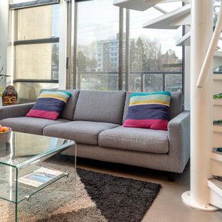 Modelo de salón tipo loft y casetón, actual, pequeño, con paredes blancas, suelo de cemento, pared multimedia y suelo gris