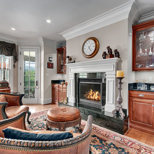 Inspiration for a timeless medium tone wood floor living room remodel in Other with gray walls and a standard fireplace