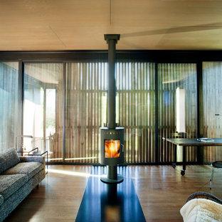 Foto de salón abierto, moderno, pequeño, con paredes marrones, suelo de madera en tonos medios, estufa de leña y marco de chimenea de metal