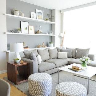 Cette image montre un salon nordique ouvert avec un mur gris et un sol en bois clair.