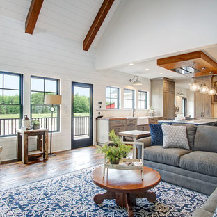 Inspiration for a farmhouse open concept dark wood floor and brown floor living room remodel in Grand Rapids with white walls, a corner fireplace and a brick fireplace