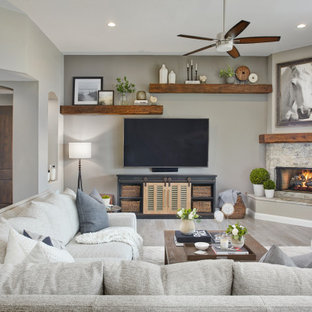 Foto de salón abierto, clásico renovado, grande, con paredes grises, suelo de baldosas de porcelana, chimenea de esquina, marco de chimenea de piedra, televisor colgado en la pared y suelo gris