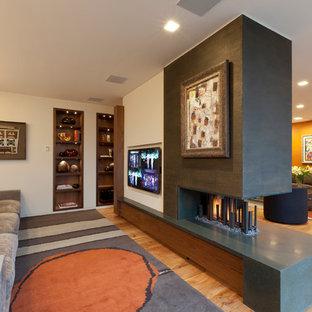 Réalisation d'un salon design ouvert avec une salle de réception, un mur blanc, un sol en bois clair, une cheminée double-face et un téléviseur fixé au mur.