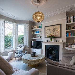 Imagen de salón cerrado, clásico renovado, de tamaño medio, con paredes marrones, chimenea tradicional, marco de chimenea de metal y televisor independiente