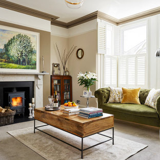 Example of a mid-sized transitional carpeted and gray floor living room design in Other with beige walls, a wood stove and a stone fireplace