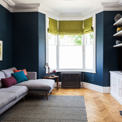 Trendy light wood floor living room photo in London with blue walls
