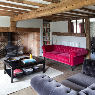 Photo of a rural formal living room in Sussex with white walls, a wood burning stove and light hardwood flooring.