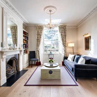 Modelo de salón para visitas abierto, tradicional, de tamaño medio, sin televisor, con suelo de madera clara, chimenea tradicional, marco de chimenea de piedra y paredes rojas