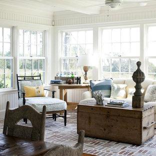 Esempio di un soggiorno costiero di medie dimensioni e aperto con pareti bianche, pavimento in mattoni e nessun camino