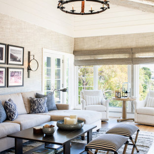 Großes, Offenes Maritimes Wohnzimmer mit beiger Wandfarbe, braunem Holzboden, braunem Boden, freigelegten Dachbalken und Holzdielenwänden in Los Angeles