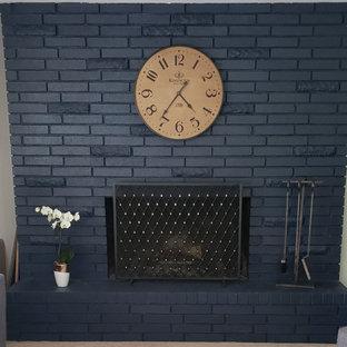 Klassisches Wohnzimmer mit blauer Wandfarbe, Teppichboden, Kamin, Kaminumrandung aus Backstein, beigem Boden und Ziegelwänden in Portland